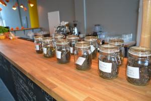 Słoiki z herbatami postawione na drewnianym blacie w lokalu