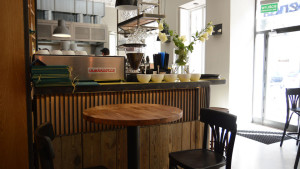 Okrągły, wysoki stolik z drewnianym blatem w restauracji