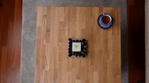 Świeczka i kawa postawione na stoliku z drewna