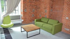 Stolik z drewnianym blatem i metalowymi nóżkami obok zielona sofa