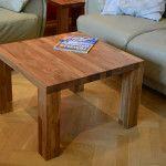 Drewniany kwadratowy stolik obok kanapy i fotela