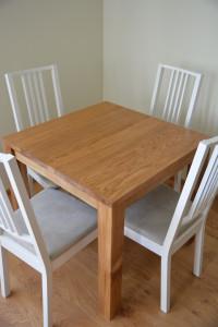 Drewniany, kwadratowy stół, białe krzesła