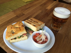 Talerz z jedzeniem i szklanka z piwem na drewnianym blacie