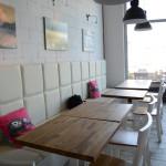 Jasne wnętrze lokalu, drewniane blaty stolików
